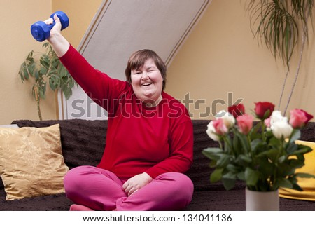 Mentally disabled woman shows her strength with a dumbbell - stock photo