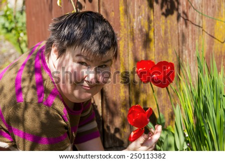 mentally disabled woman smells on a flower - stock photo