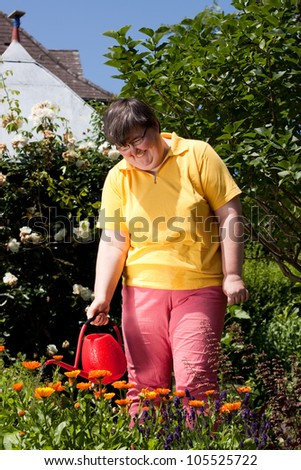 mentally disabled woman stands in the garden and  poured  flowers - stock photo