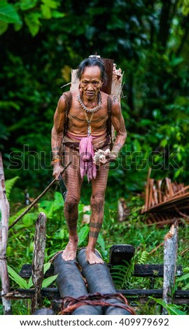 MENTAWAI PEOPLE, WEST SUMATRA, SIBERUT ISLAND, INDONESIA â?? 03 OKTOBER 2011: Man Mentawai tribe comes back home from hunting. 03 October, 2011. West Sumatra, Siberut island, Indonesia. - stock photo