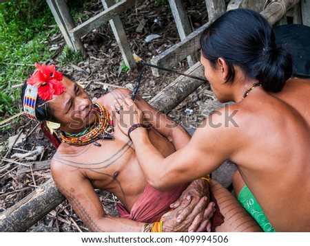 MENTAWAI PEOPLE, WEST SUMATRA, SIBERUT ISLAND, INDONESIA  03 OKTOBER 2011: Men Mentawai tribe make tattoo. 03 October, 2011. West Sumatra, Siberut island, Indonesia. - stock photo