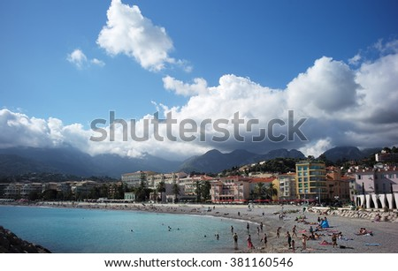 MENTON, FRANCE - September 19, 2015: Beach on shores of azure sea in Menton with hotels against mountains covered with clouds, horizontal photo
