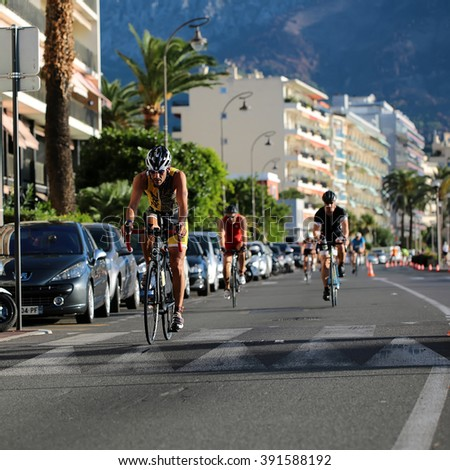 Menton, Roquebrune Cap Martin, France - September 20, 2015: riders cyclists compete in duathlon athletic event team bicycle racing sport on paved roads on streetscape background, square picture  - stock photo