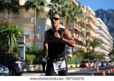 Menton, Roquebrune Cap Martin, France - September 20, 2015: runner ahead in black suit sunglasses competes in duathlon running cross city on paved roads on streetscape background, horizontal picture  - stock photo