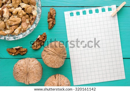Menu background. Cook book. Recipe notebook with walnuts on turquoise wooden texture - stock photo
