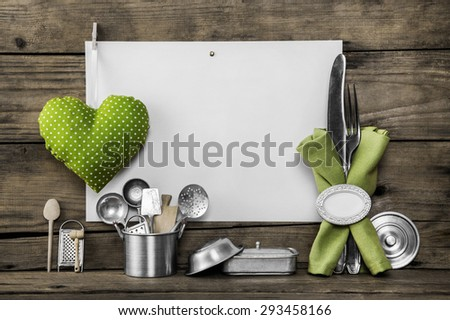 Menu card with old kitchen utensils, white placard, apple green doted heart, equipment and pots on an old wooden background. - stock photo