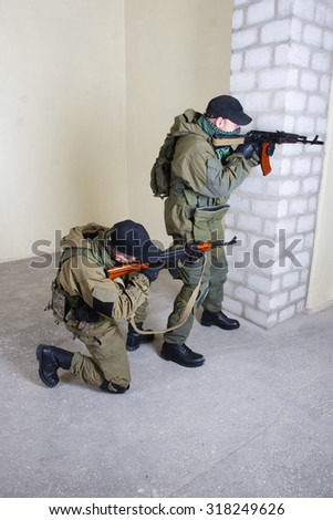 mercenary with AK-47 rifle inside the building  - stock photo
