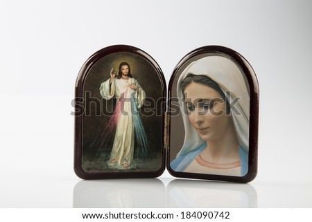 Merciful Jesus and Our Lady of Medjugorje, the Blessed Virgin mary, icons in a wooden rounded case isolated on white backgrounds with shady reflection on white table. - stock photo