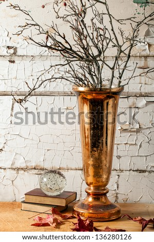 Mercury glass copper vase with dried twiggy branches and autumn leaves against a rustic old wall with peeling white paint. Fall or winter centerpiece in a grunge or shabby chic style. - stock photo