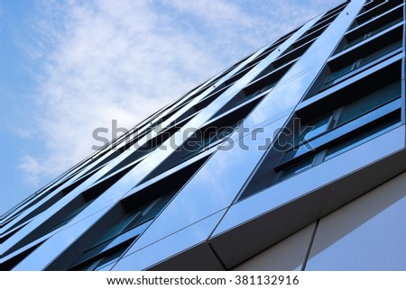 Merger of sky with reflecting semi-matte facade panels. Low angle view of contemporary building fragment. Abstract architectural composition. - stock photo