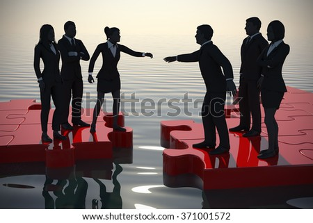 Merger of two teams on a jigsaw puzzle at sunset. Two teams of successful executives merging on a jigsaw puzzle at sunset showing a partnership. - stock photo