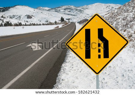Merging Lanes Sign:  Motorists are warned to move left as the right lane ends along a mountain road.   - stock photo