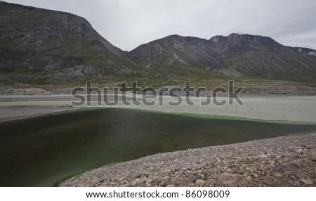 Merging rain water and melting water rivers, Greenland - stock photo