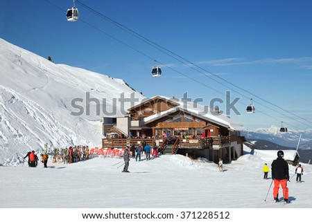 "MERIBEL, FRANCE - JAN 24, 2016: The restaurant ""Le Sittelle"" with cabins of cable car in Les 3 vallees ski resort"