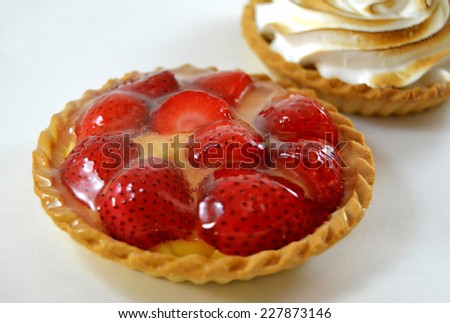 Meringue  and strawberries tarts on white background