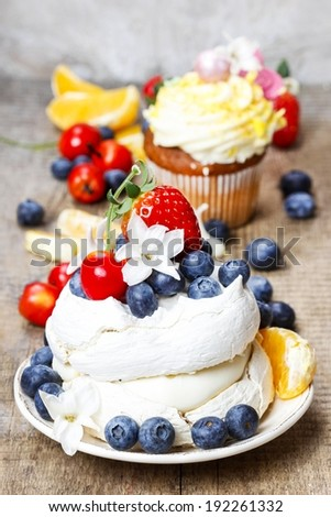 Meringue cake decorated with fresh fruits, standing on wooden table - stock photo