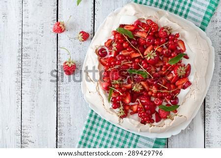 "Meringue Cake ""Pavlova"" with cream and berries. Top view - stock photo"