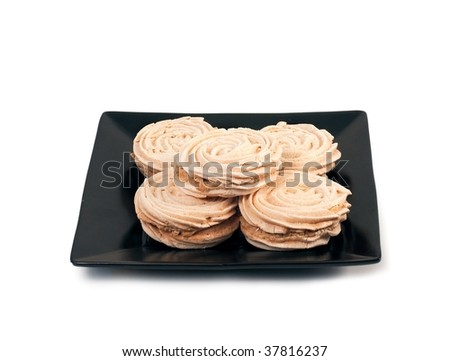Meringue cookies on a black plate isolated on white - stock photo