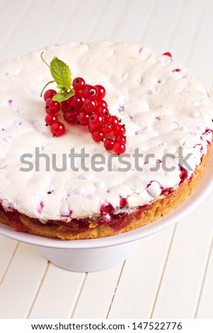 Meringue red currant cake on white table