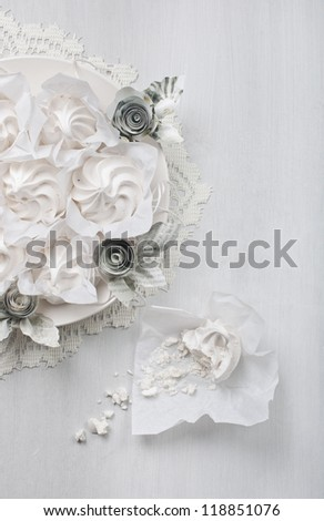 Meringues in paper packing on a plate and a broken piece of meringue on a white board - stock photo