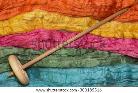 Merino and silk fibers with a handspindle - stock photo