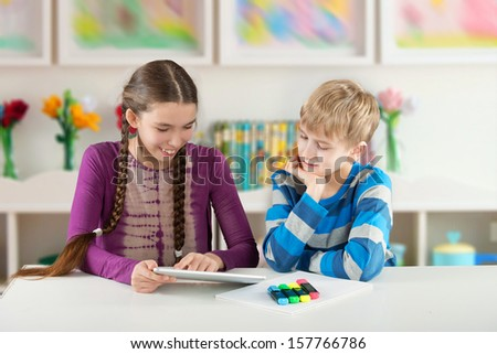 Merry children sitting by the table and looking at a Pad Tablet PC screen