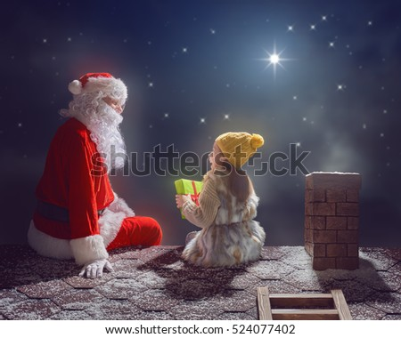 Merry Christmas and happy holidays! Cute little child girl and Santa Claus sitting on the roof and looking at snowfall. Christmas legend concept.