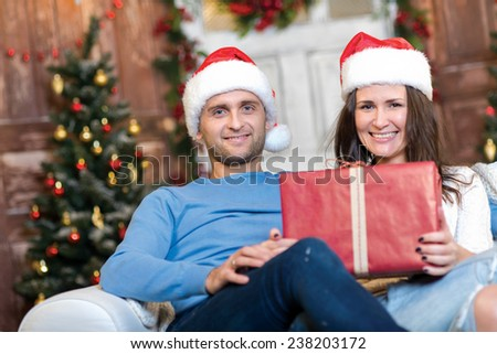Merry Christmas and Happy New Year. Couple in love is sitting in festive Christmas decorated living room. Both are looking in the camera with smiles and fun New Year mood