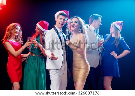 Merry Christmas and Happy New Year! Party and celebration. Group of six happy smiling friends having fun together, singing karaoke in the club. - stock photo