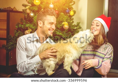 Merry Christmas and Happy New Year. Young beautiful couple are playing with their dog  in festive New Year living room just before the Christmas. - Caucasian people - Animal, people, holiday concept - stock photo