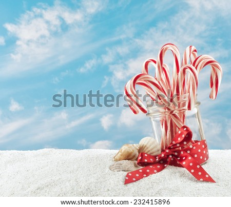 Merry Christmas at the beach with Candy Canes in a Jar in the Sand and sky background with room or space for copy, text, your words.  Horizontal but can be crop to vertical - stock photo