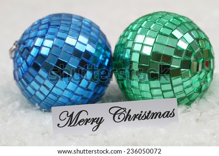 Merry Christmas card with blue and green baubles on snowy surface  - stock photo