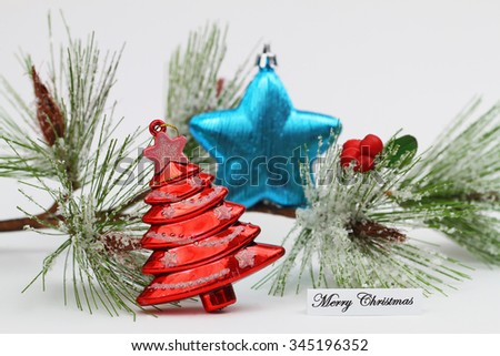 Merry Christmas card with colorful Christmas decorations and pine covered in snow