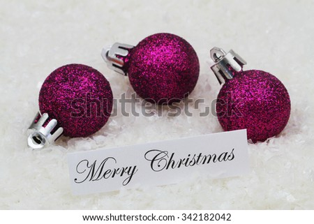 Merry Christmas card with purple baubles covered with glitter on snowy surface