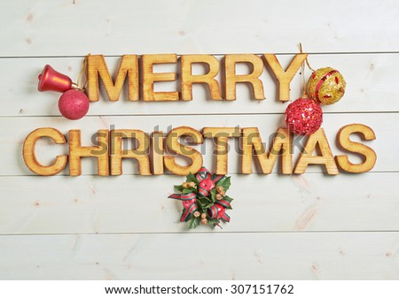 Merry Christmas composition of the wooden letters surrounded with the multiple decorations over the white colored wooden boards surface - stock photo