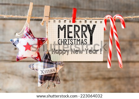 Merry christmas Happy New Year inscription. Merry Christmas Happy New Year inscription on checkered paper attach to rope  - stock photo