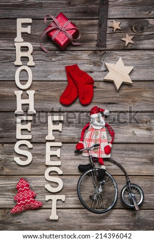 Merry Christmas in german text with santa in red and wooden decoration. - stock photo