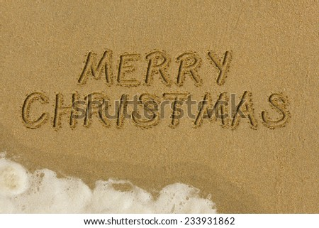 Merry Christmas message written in the sand - stock photo