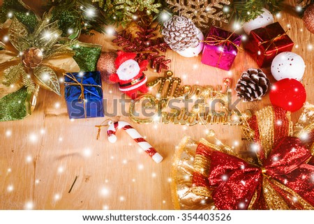 Merry Christmas on snow and wooden background
