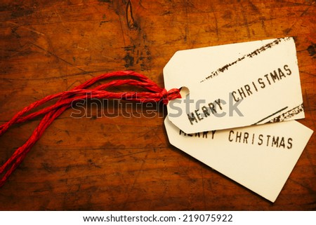 Merry Christmas tags on old wooden surface.