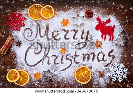 Merry Christmas text made with flour with decorations on cutting board - stock photo