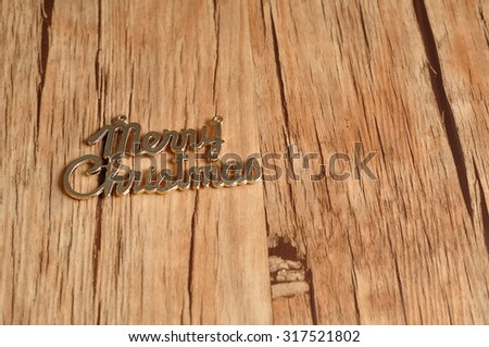 Merry Christmas text on a wooden background with open space for additional text