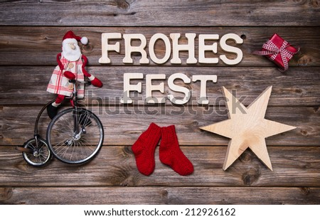 Merry christmas text on wood with rustic funny red decoration with santa on wood. - stock photo