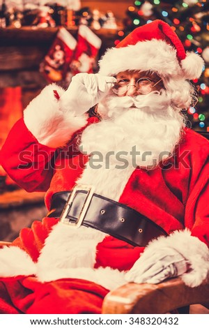 Merry Christmas! Traditional Santa Claus sitting at his chair and adjusting his eyeglasses with fireplace and Christmas Tree in the background
