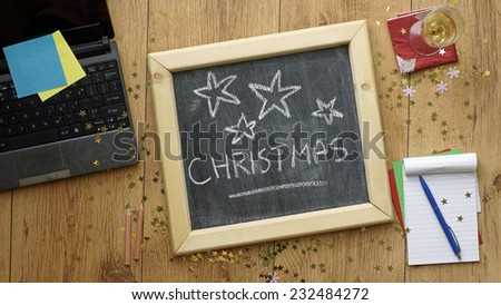Merry christmas written on a chalkboard at the office - stock photo