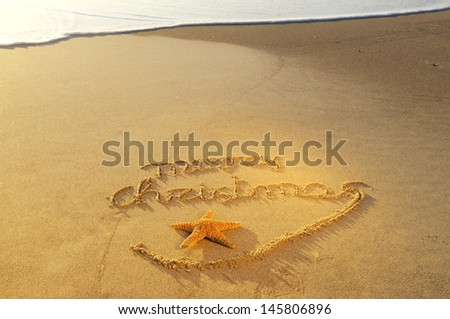 Merry Christmas written on sand - stock photo