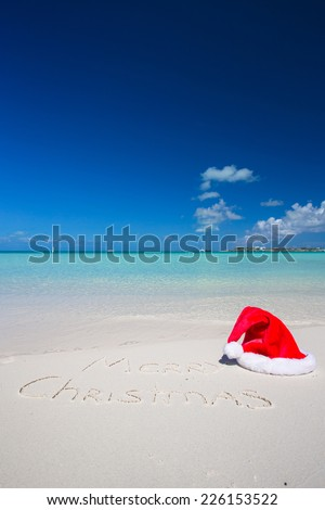 Merry Christmas written on tropical beach white sand with xmas hat - stock photo
