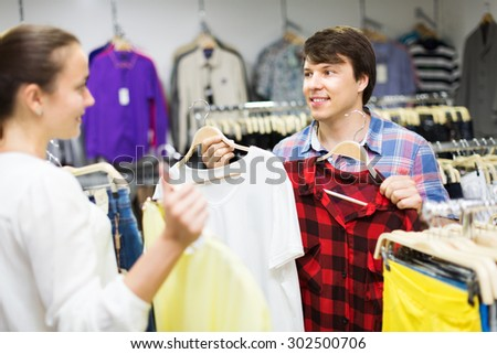 Merry couple choosing clothes at store