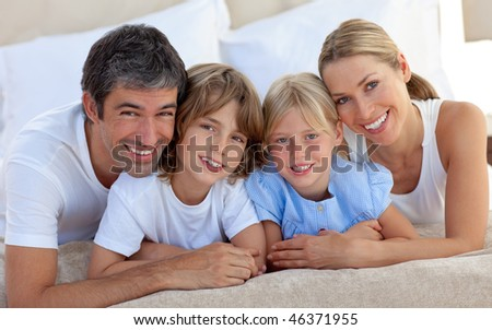 Merry family having fun lying on a bed - stock photo