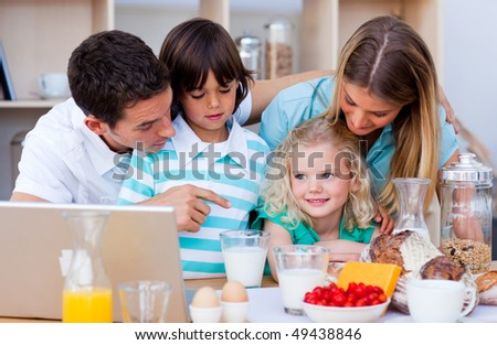 Merry family using laptop during the breakfast in the kitchen - stock photo